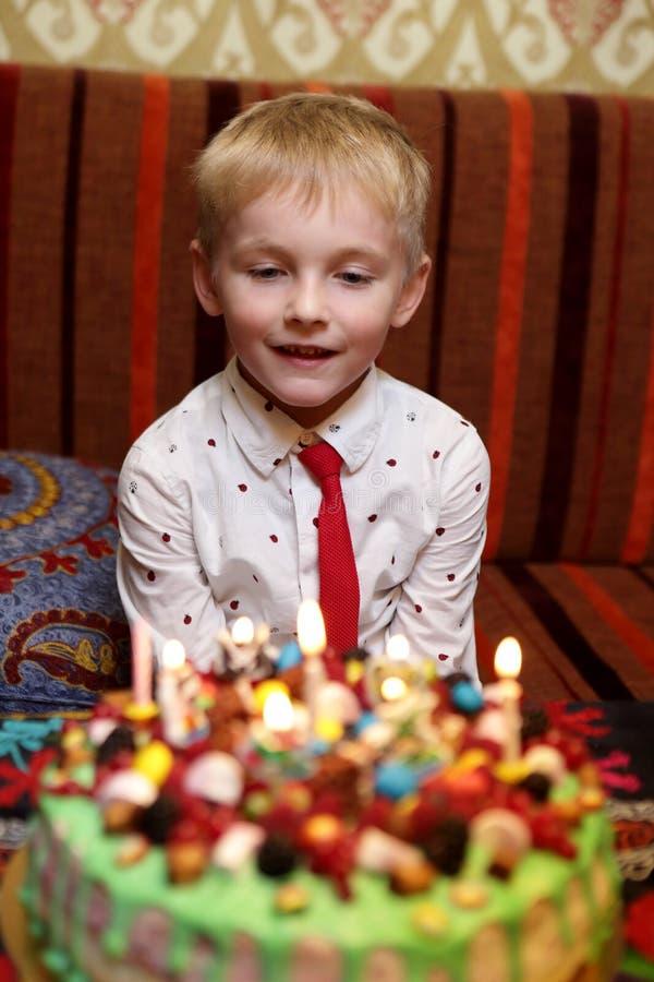 Niño que mira la torta de cumpleaños imágenes de archivo libres de regalías