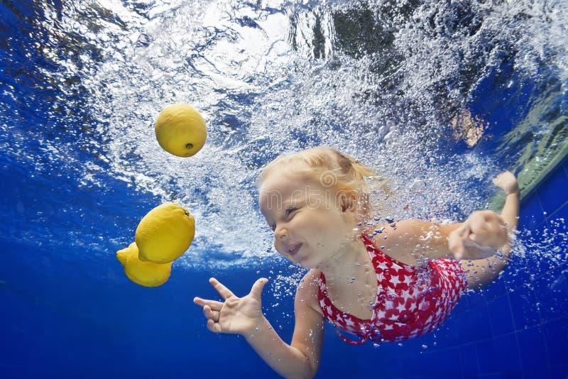 Niño que nada bajo el agua en la piscina azul para el limón amarillo fotografía de archivo