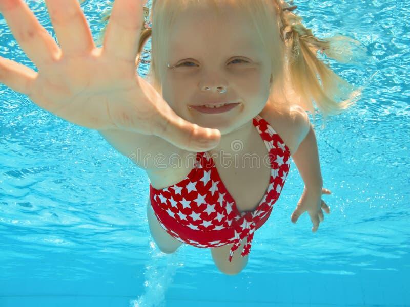 Niño que nada bajo el agua en piscina imagenes de archivo