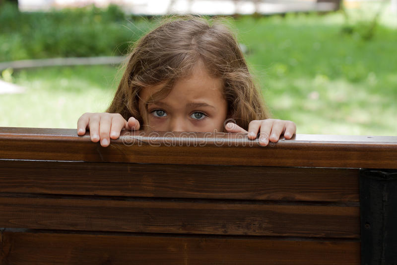 Niño que oculta detrás de un BenchIn foto de archivo