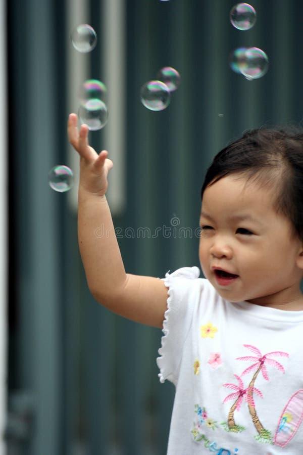 Niño que persigue burbujas fotografía de archivo libre de regalías