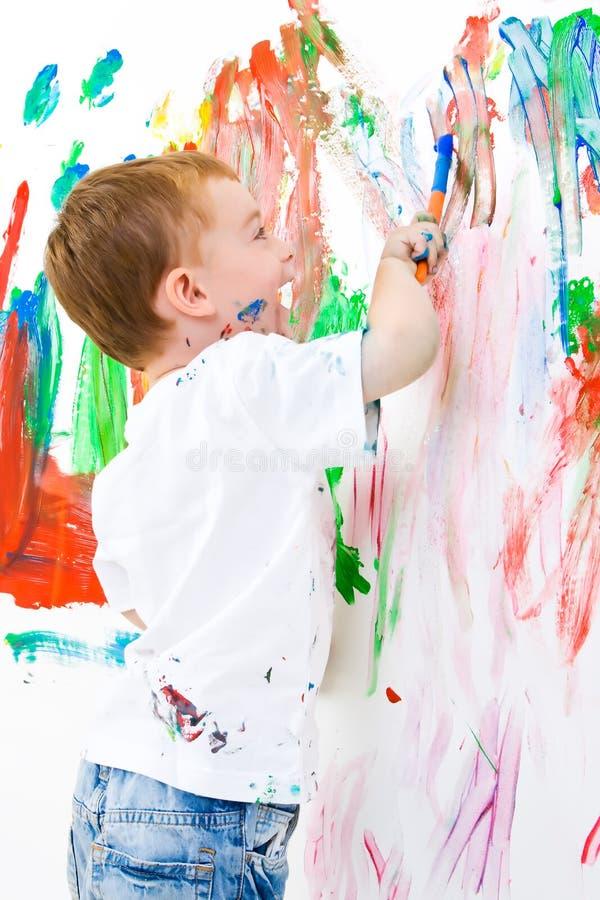 Niño que pinta y que se divierte mucho imagen de archivo libre de regalías