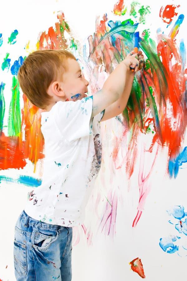 Niño que pinta y que se divierte mucho imagen de archivo