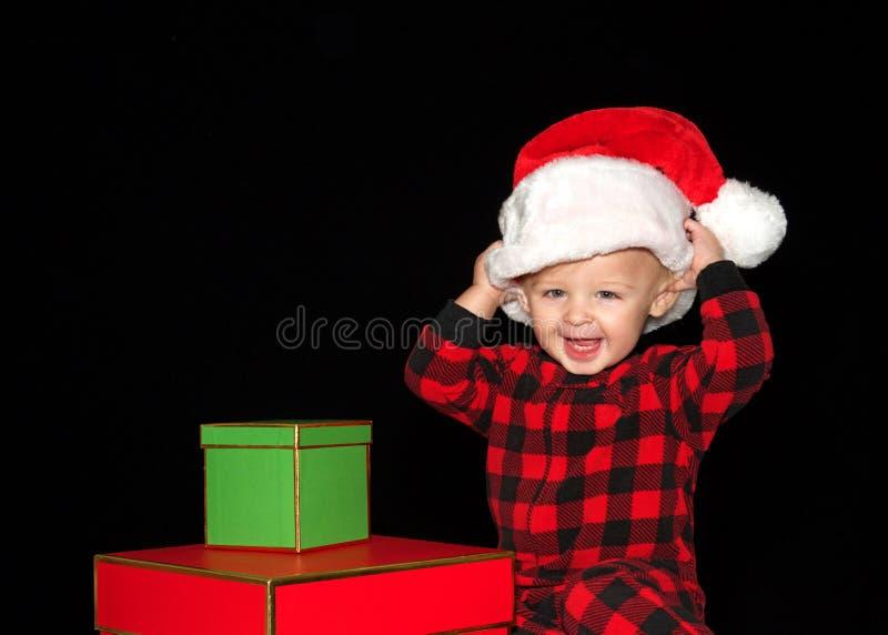 Niño que pone en un sombrero de santa con los regalos de Navidad fotos de archivo libres de regalías