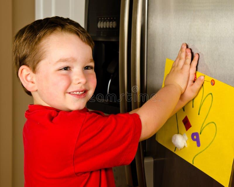 Niño que pone su arte para arriba en el refrigerador de la familia foto de archivo
