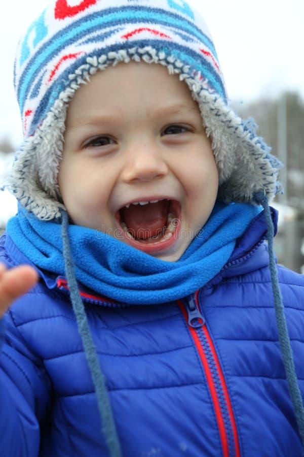 Niño que ríe hacia fuera ruidosamente imagen de archivo