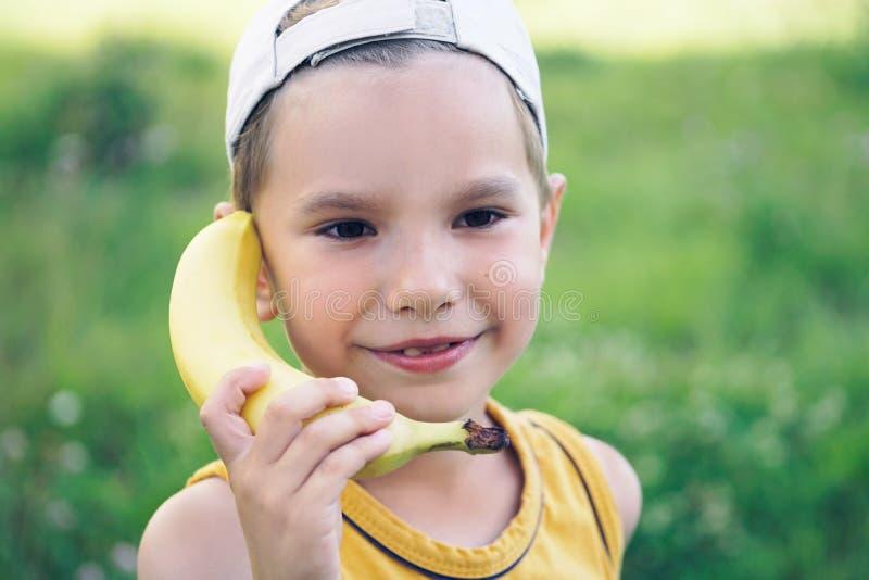 Niño que ríe mientras que juega finja con un teléfono de madera del plátano imagen de archivo libre de regalías
