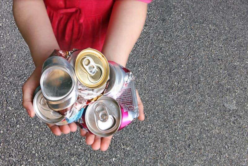 Niño que recicla las latas de aluminio imagenes de archivo