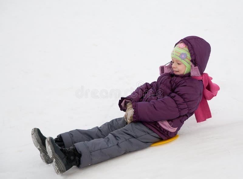 Niño que resbala en la nieve imagen de archivo