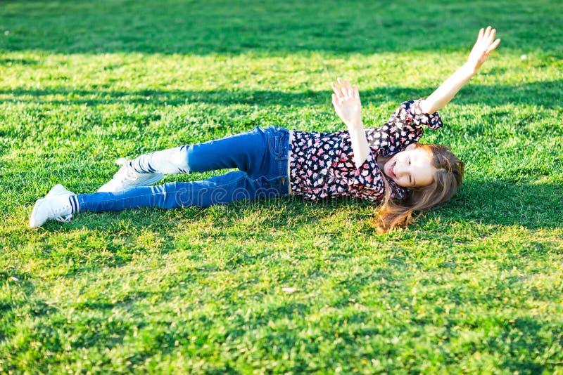 Niño que rueda abajo la colina en hierba fotos de archivo libres de regalías