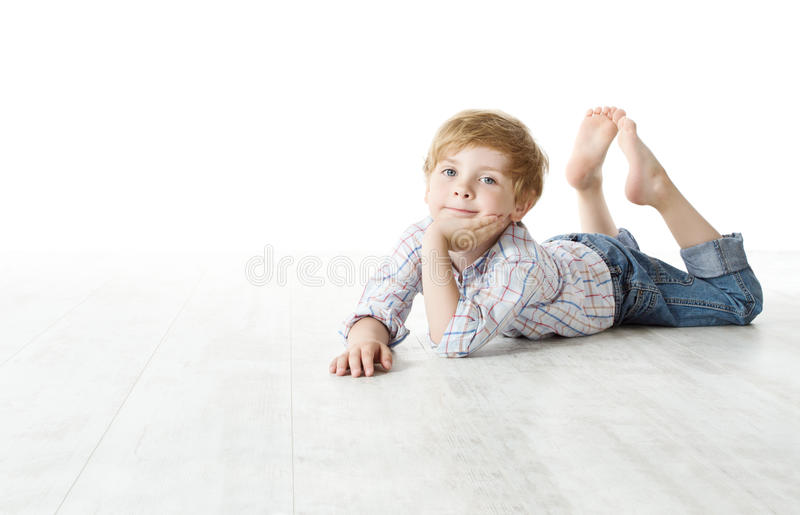Niño que se acuesta en suelo y que mira la cámara imagen de archivo