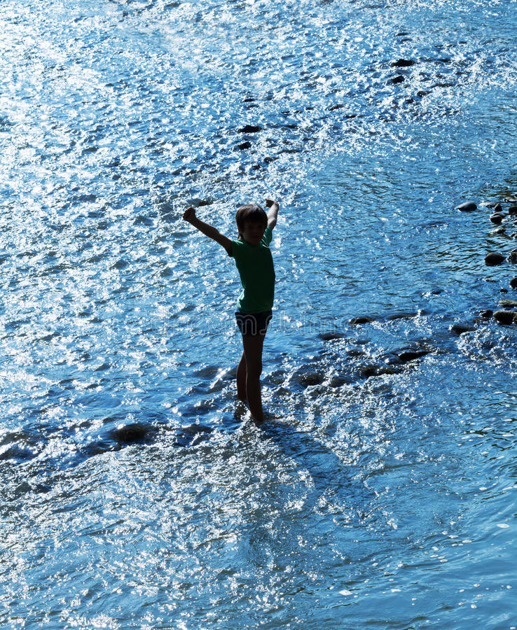 Niño que se coloca en el agua que chispea en contraluz imagen de archivo libre de regalías