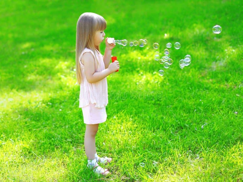 Niño que se coloca en las burbujas de jabón de la hierba que soplan en verano imagenes de archivo