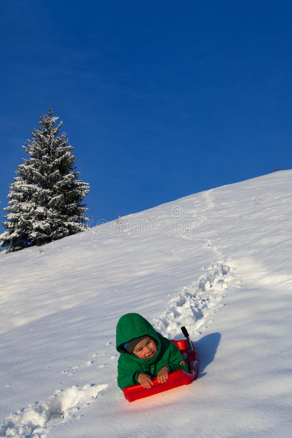 Niño que se divierte en invierno, en un trineo imagenes de archivo