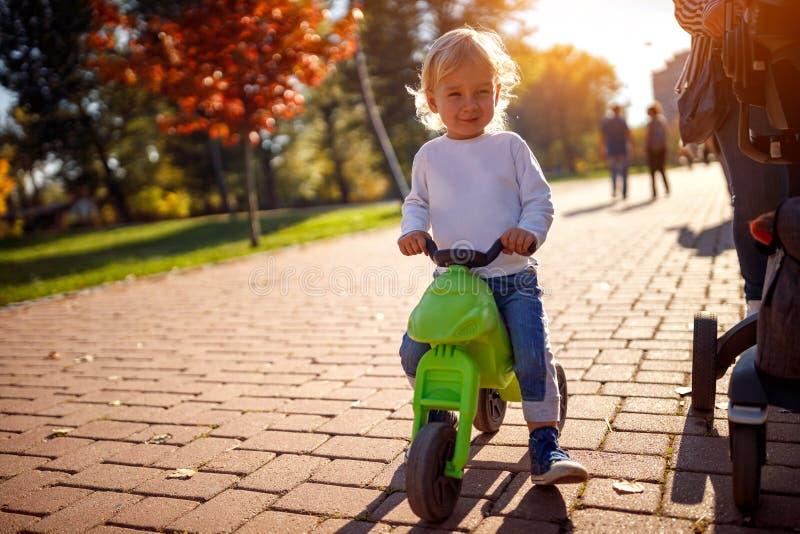 Niño que se divierte en las bicis en parque del otoño imagenes de archivo