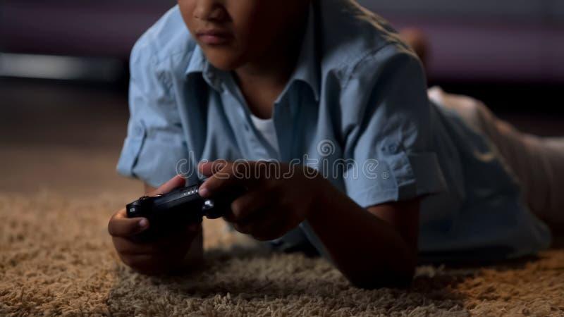 Niño que se entretiene jugando a los videojuegos en la consola, dependencia virtual imagenes de archivo