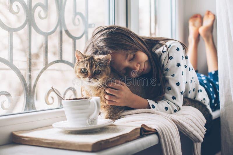 Niño que se relaja con un gato en un travesaño de la ventana imagenes de archivo