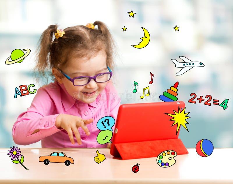 Niño que se sienta con la tableta y que aprende los wi imagen de archivo