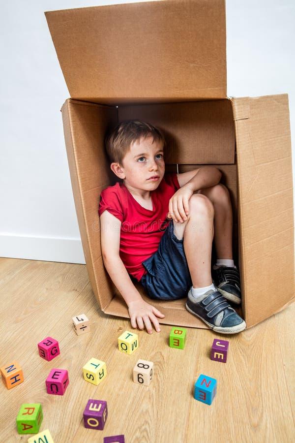 Niño que se sienta en caja, pensando en la escuela, buscando para la confianza imagenes de archivo