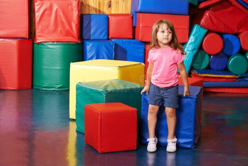 Niño que se sienta en el gimnasio del preescolar imagen de archivo