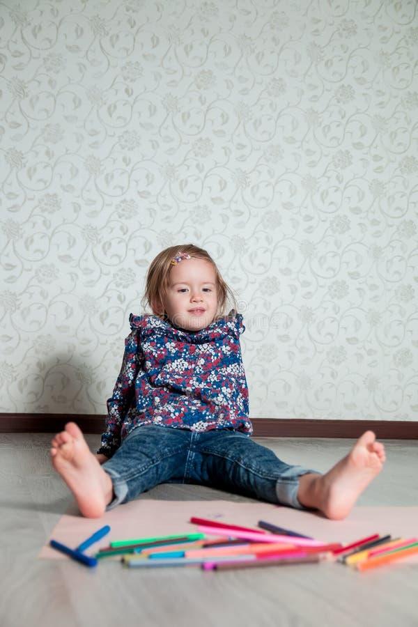 Niño que se sienta en el piso cerca de los creyones y del papel Dibujo de la niña, pintura Concepto de la creatividad Feliz, sonr imágenes de archivo libres de regalías