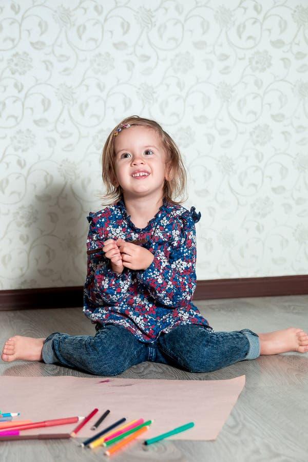 Niño que se sienta en el piso cerca de los creyones y del papel Dibujo de la niña, pintura Concepto de la creatividad Feliz, sonr imagenes de archivo