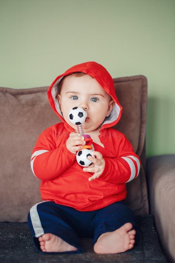 niño que se sienta en el sofá y que sostiene el juguete del fútbol del fútbol fotografía de archivo