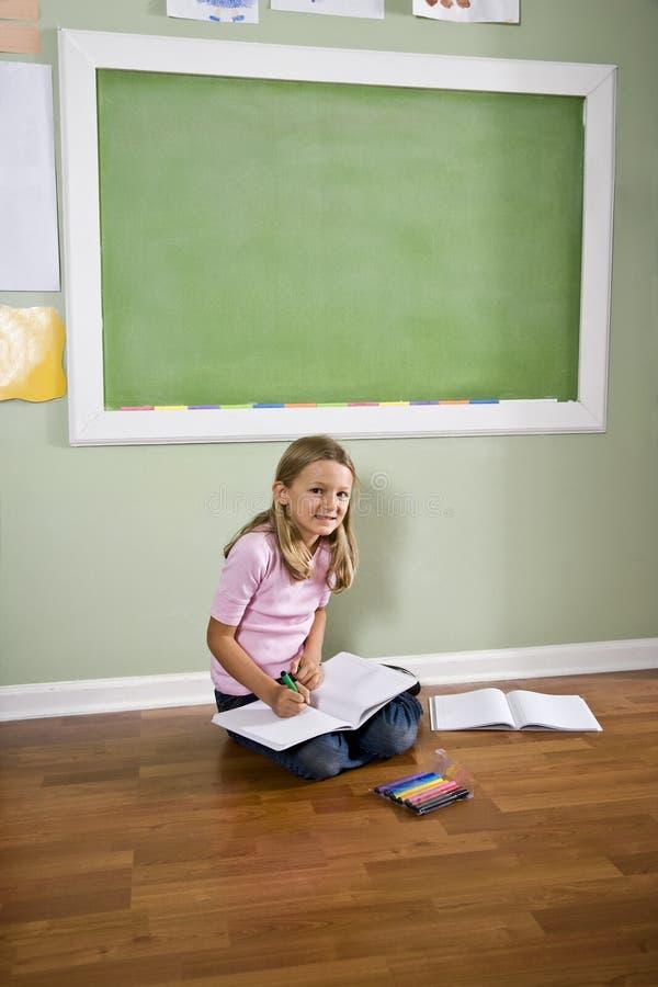 Niño que se sienta en la escritura del suelo en sala de clase foto de archivo libre de regalías