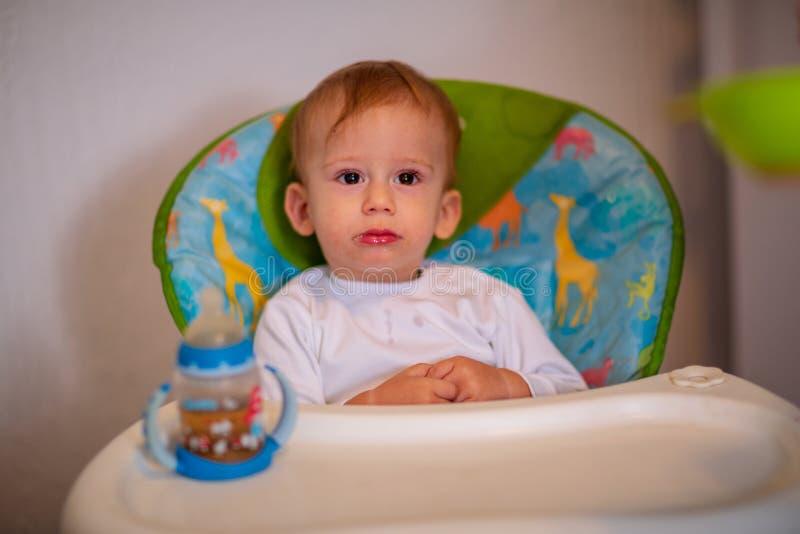 Niño que se sienta en la silla para alimentar y el agua potable con foto de archivo libre de regalías