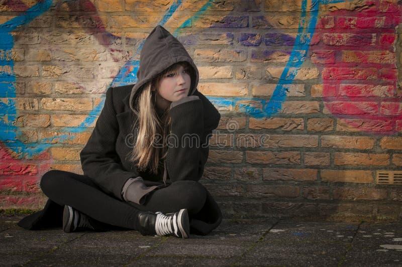 Niño que se sienta en la tierra foto de archivo