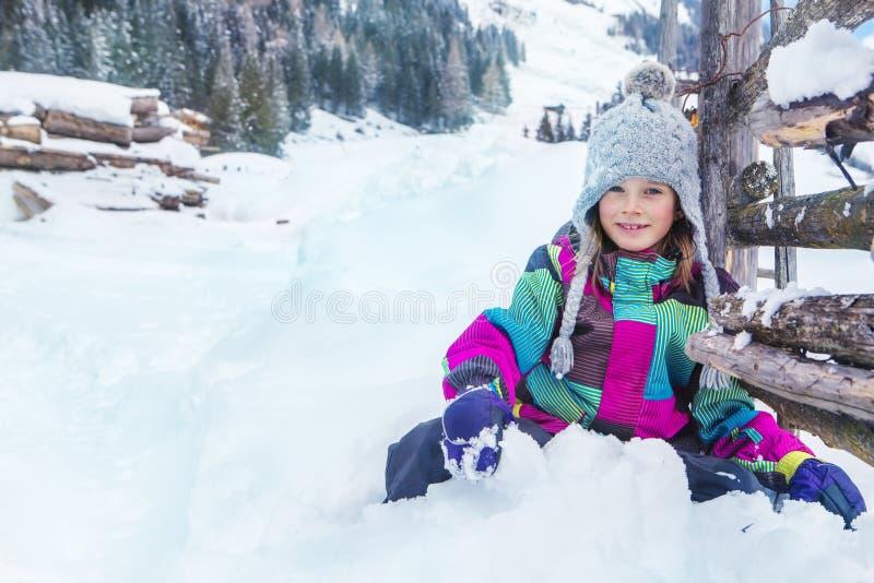 Niño que se sienta en nieve imagenes de archivo