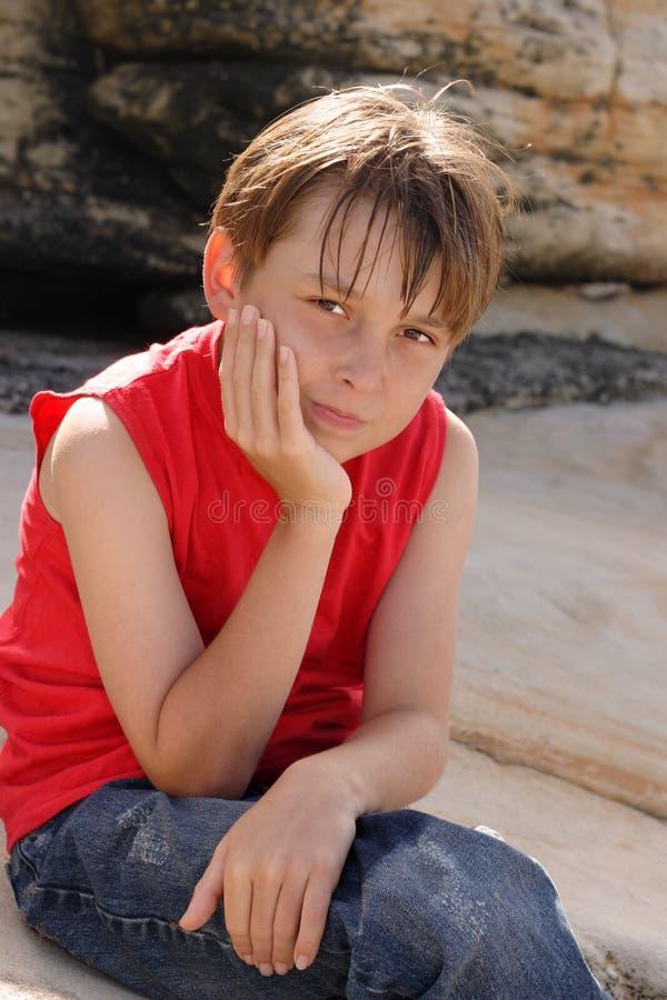 Niño que se sienta en rocas imagen de archivo libre de regalías