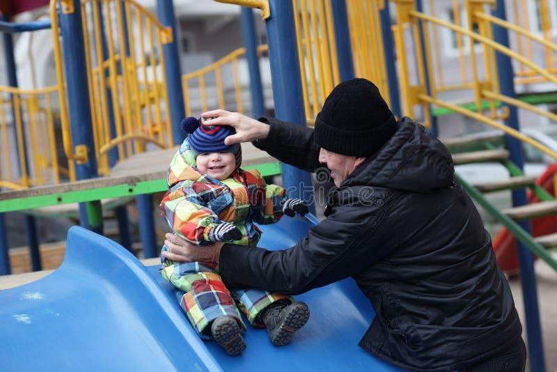 Niño que se sostiene de abuelo en diapositiva imagen de archivo