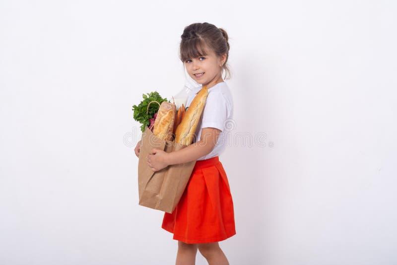 Niño que sostiene el bolso de ultramarinos de papel por completo de las verduras leche, pan Niño feliz con el bolso de ultramarin imagen de archivo libre de regalías