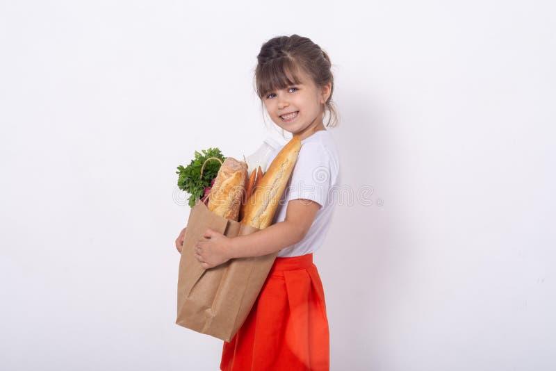 Niño que sostiene el bolso de ultramarinos de papel por completo de las verduras leche, pan Niño feliz con el bolso de ultramarin imágenes de archivo libres de regalías