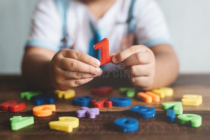 Niño que sostiene el juguete plástico número uno, ella está aprendiendo contar imagenes de archivo