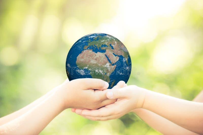 Niño que sostiene el planeta de la tierra en manos imágenes de archivo libres de regalías