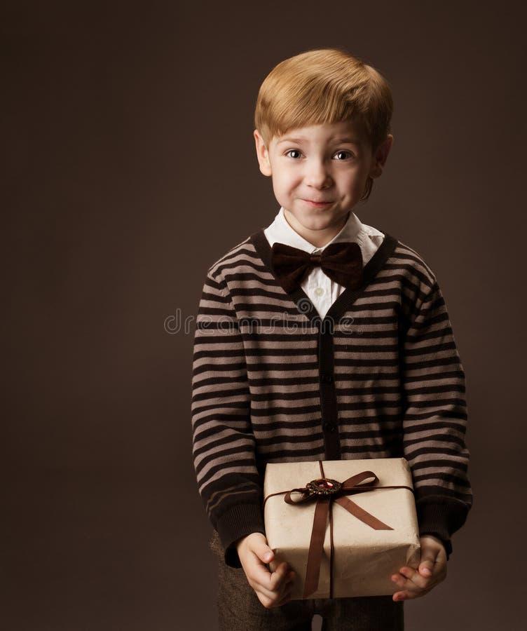 Niño que sostiene el rectángulo de regalo imagenes de archivo