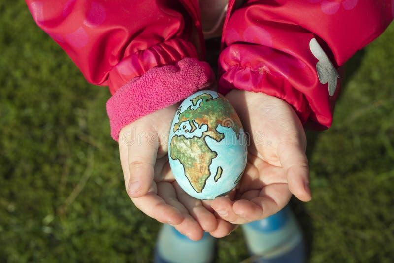 Niño que sostiene un huevo con la tierra del planeta pintada en ella en un día soleado al aire libre foto de archivo