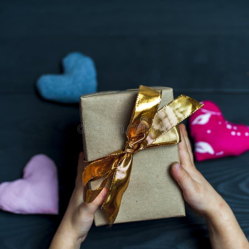 Niño que sostiene una caja de regalo con la cinta de oro imagenes de archivo