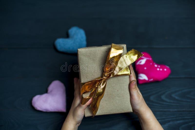 Niño que sostiene una caja de regalo con la cinta de oro imagen de archivo libre de regalías
