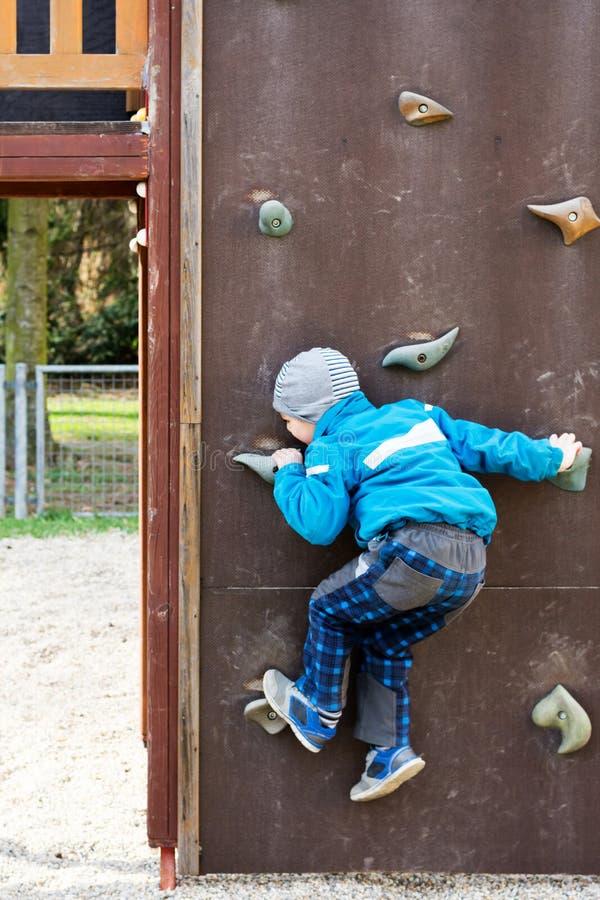 Niño que sube una pared en un patio fotografía de archivo
