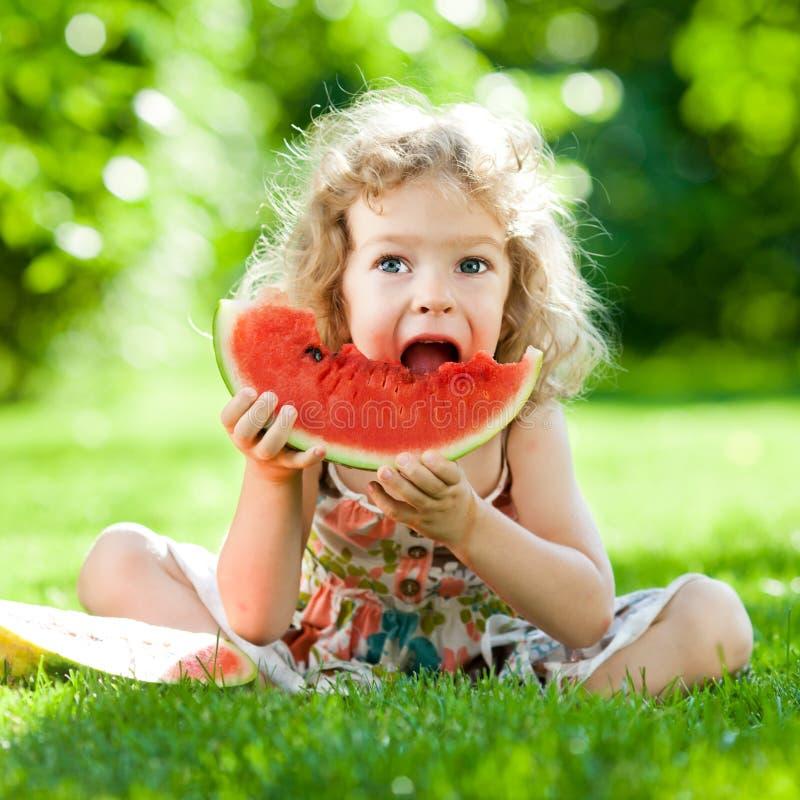 Niño que tiene comida campestre en parque foto de archivo