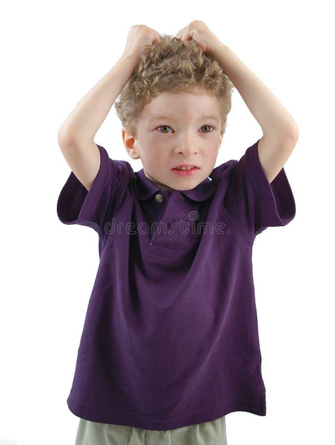 Niño que tira de su pelo fotografía de archivo