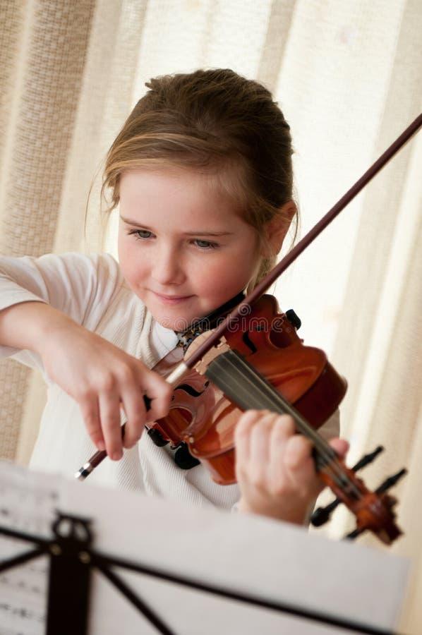 Niño que toca el violín en el país foto de archivo