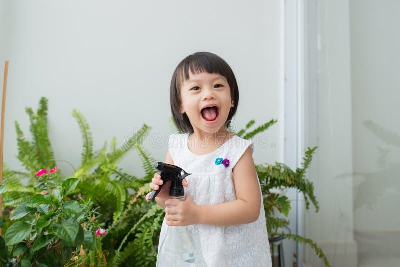 Niño que toma el cuidado de plantas Spr de riego de la niña linda primer fotos de archivo libres de regalías