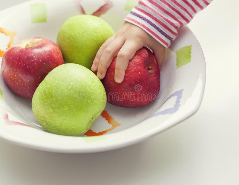 Niño que toma la manzana del cuenco imagenes de archivo
