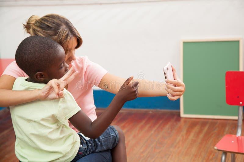 Niño que toma una foto con su profesor fotografía de archivo