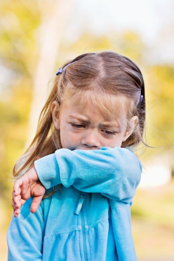 Niño que tose o que estornuda en el brazo foto de archivo libre de regalías