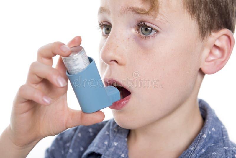 Niño que usa el inhalador para el asma Fondo blanco imagen de archivo libre de regalías